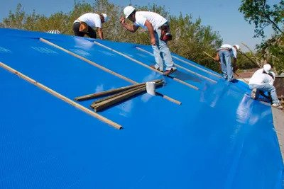 Emergency Roofing Services putting a tarp on a roof repair.